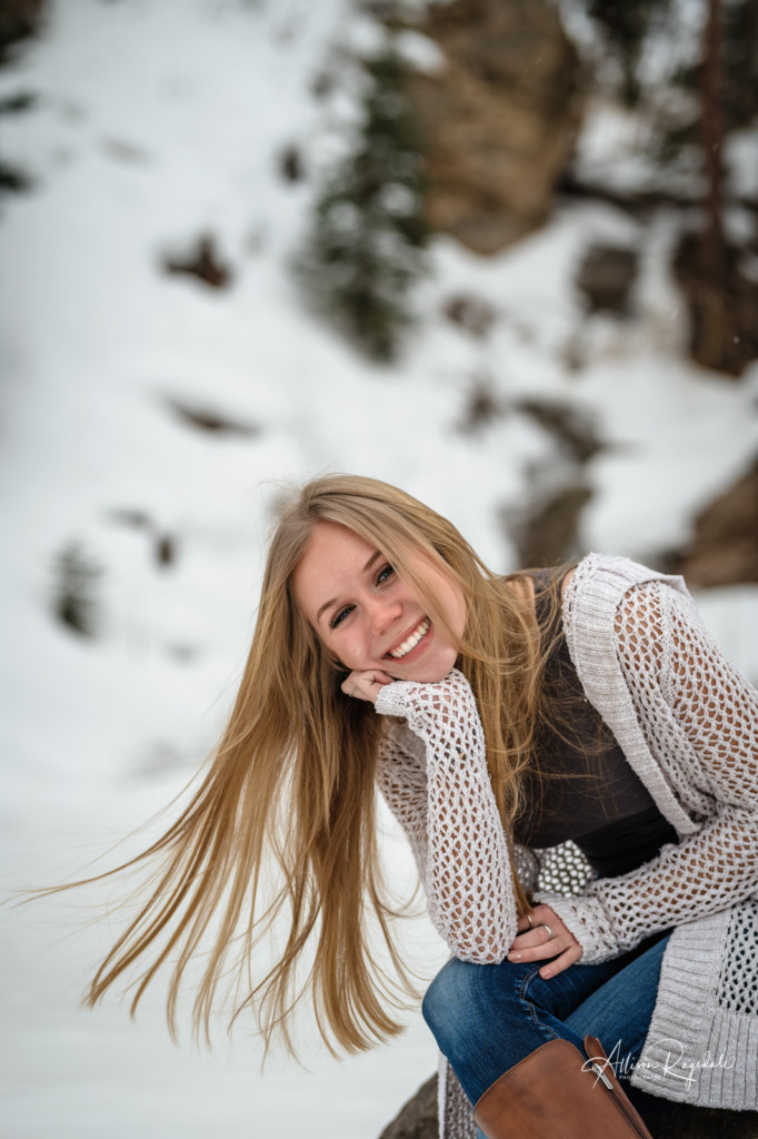 senior girl in snow hair blowing in wind picture