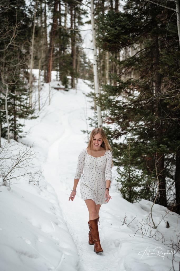 senior girl walking down snowy path colorado portrait