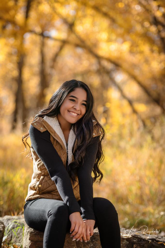 senior girl photo sitting on rock falls colors