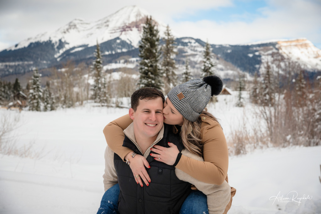 engagement photo piggy back ride colorado winter engineer mountain