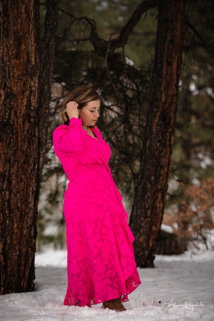 mom in bright pink dress in colorado pine trees picture