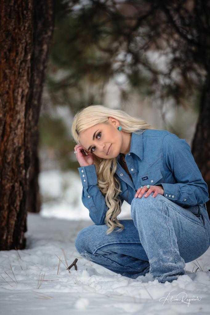 teenage daughter kneeling in snow portrait