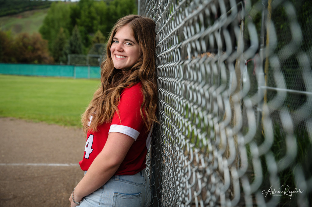 senior girl pic leaning on chain link fence on softball field
