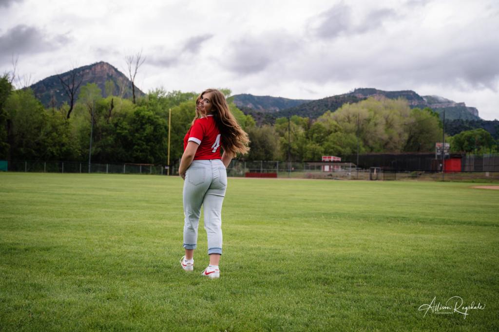 walking away on softball field hairflip durango co mountain background senior picture